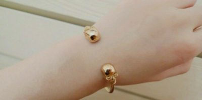 dual skull cuff bracelet on female wrist